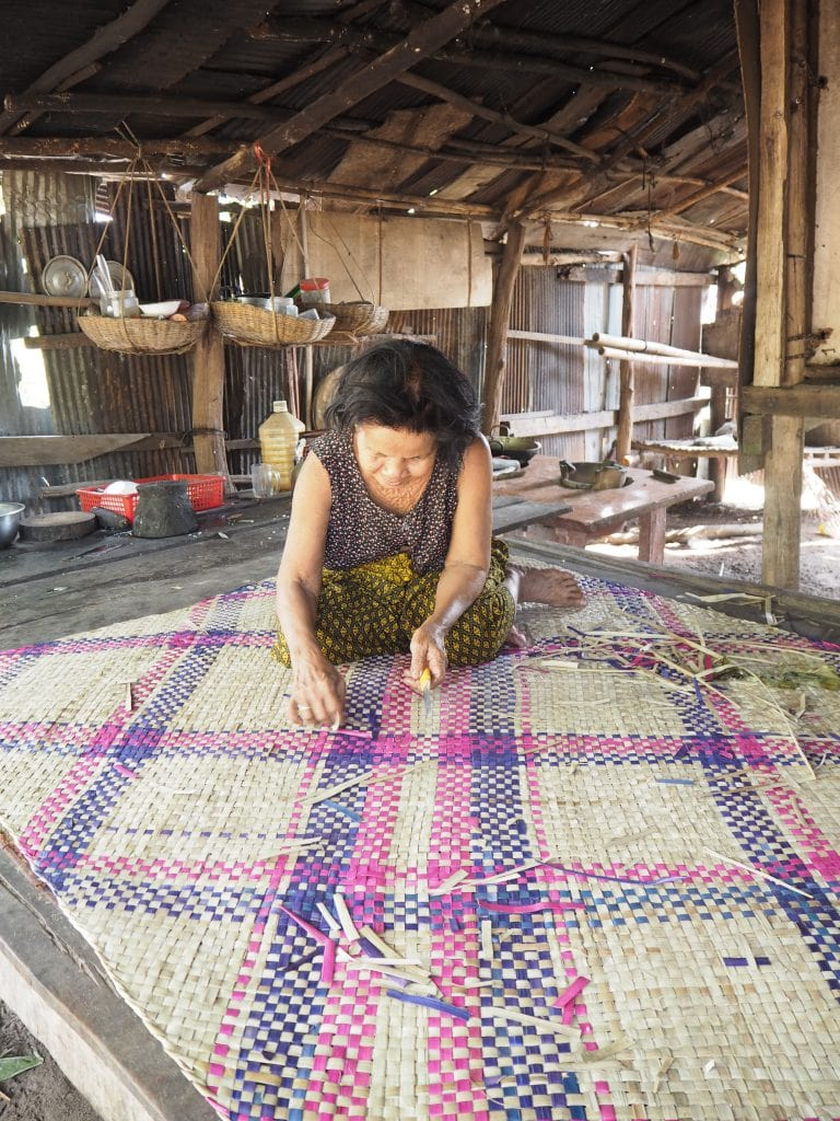 A women who was helped by the Shinta Mani Foundation making a rattan mat