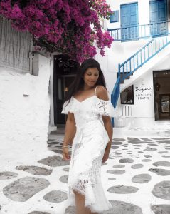 Bonnie Rakhit in Mykonos wearing very.co.uk white lace dress with bougonvillea flowers